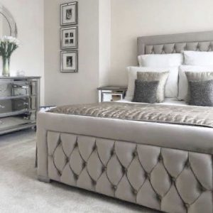 Silver upholstered bed and headboard with buttoning detail