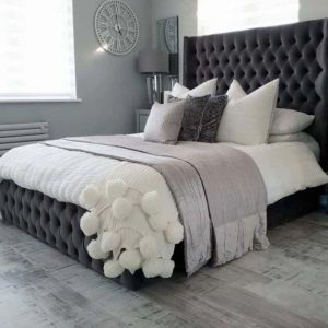 Tall wingback bed frame with deep buttoned headboard and footboard
